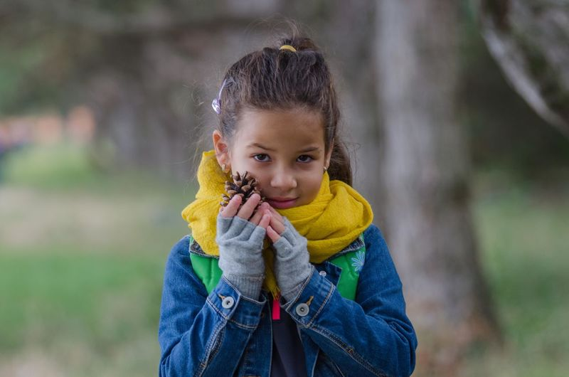 Portrait Of Girl Holding Pine Cone While Standing Against Trees