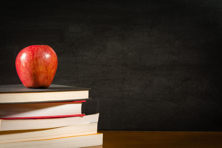 Stack of books and a red apple on a desk front of a blank blackboard Education Books Apple Red Backgrounds Blackboard  Chalkboard Chalk Black Board Desk Blank Copy Space Studying Knowledge Learning Teaching Schooling Literature Hardcover Classroom School Fruit Food Back To School