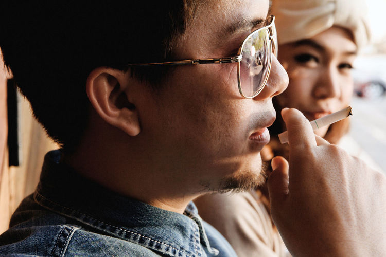 A shot of a young couple dating outdoor Couple Couple - Relationship Couple In Love Asian Girl Asian People Thai Lifestyles Man Girl Women Portrait Headshot Young Adult Real People Close-up Dating Smoke Smokeing Cigarette  Men Indoors  Males  Leisure Activity Human Body Part Glasses Young Men Holding Mid Adult Men People Applying Smoking - Activity Beard Human Face Body Part