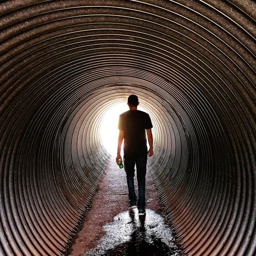 Walking through a tunnel in Texas. EyeEmNewHere Walking Away Dim Light Dark Light Puddle Tunnel EyeEm Selects Full Length Real People Lifestyles One Person Pattern Leisure Activity Men Silhouette Walking Standing Rear View Architecture Sunlight Casual Clothing Day First Eyeem Photo