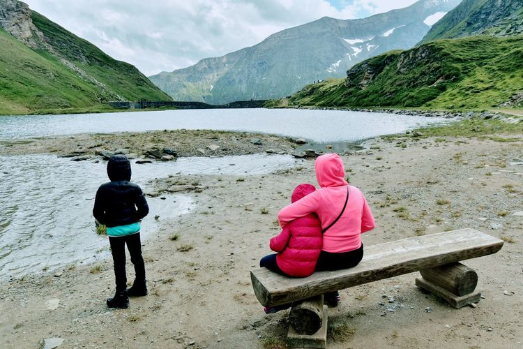 Rear view of women sitting by mountains against sky
