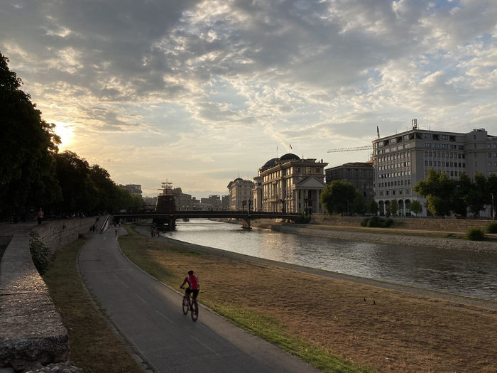People riding bicycle on road by river against sky