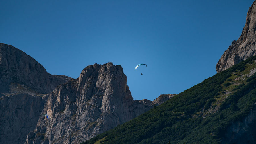 Austria Paragliding Adventure Beauty In Nature Blue Clear Sky Copy Space Day Extreme Sports Flying Formation Low Angle View Mid-air Mountain Mountain Range Nature No People Outdoors Rock Rock Formation Scenics - Nature Sky Solid Tranquil Scene Tranquility