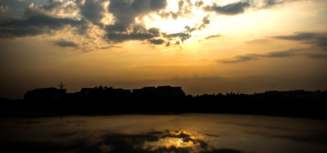 Sunset Sky Cloud - Sky Water Beauty In Nature Scenics - Nature Silhouette Building Exterior Built Structure Orange Color No People Tranquil Scene Tree Building Plant Idyllic Outdoors Nature Architecture Tranquility