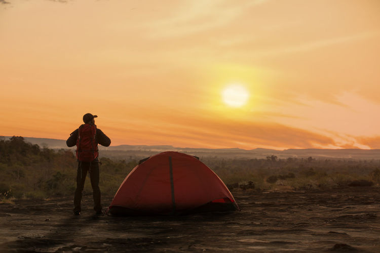 Backpacker with tent in camping site with sunset or sunrise background Sunset Sky Real People One Person Leisure Activity Beauty In Nature Lifestyles Scenics - Nature Orange Color Standing Adventure Full Length Nature Land Trip Sun Holiday Vacations Tranquility Outdoors Tent Camping