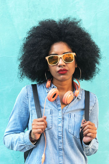 Portrait of beautiful afro american woman in the street. Adult African Afro American Beautiful City Life Copy Space Hair Lifestyle Looking At Camera Woman Backpack Black Casual Clothing Curly Hair Denim Denim Jacket Ethnic Outdoors People Portrait Serious Street Sunglasses Urban