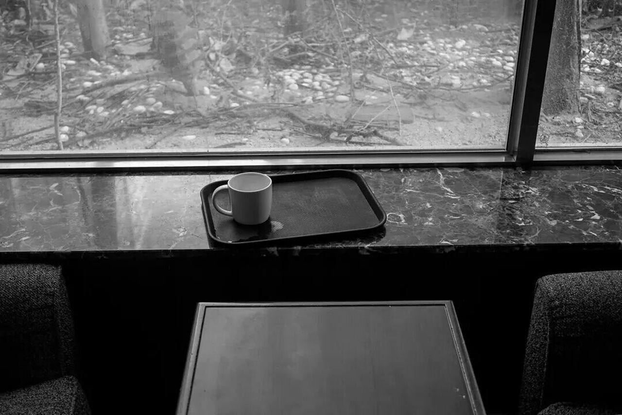 High angle view of coffee cup in tray on counter by window