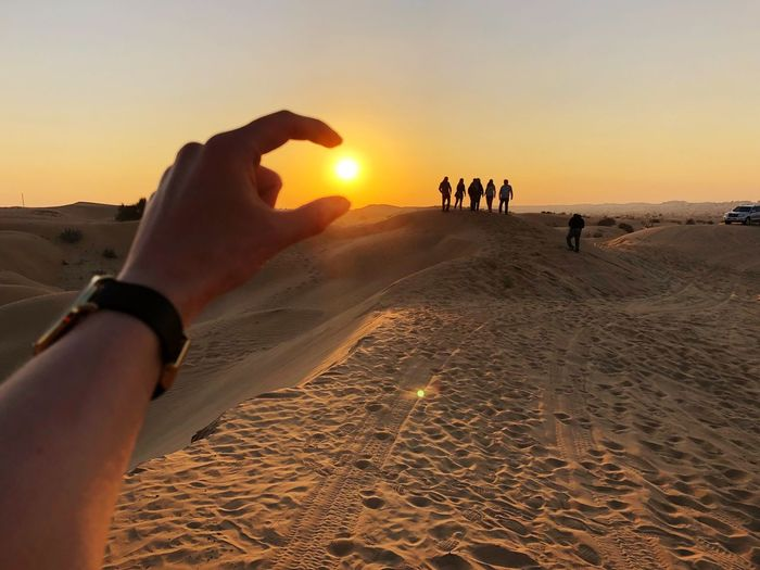 Sunset Sand Real People Nature Beach Leisure Activity Lifestyles Human Hand Outdoors Desert Beauty In Nature Human Body Part Scenics Sand Dune Vacations Sun Landscape Silhouette Men Sky