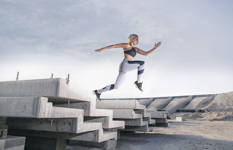 Middle Eastern Girl with short braided hair jumping of a stack of blocks on a construction site wearing gray and black fitness outfit on a hot bright sunny day. Exercising Jumping Off Rocks Sitting Arms Outstretched Arms Raised Balance Bright Day Day Dusty Fitness Model Full Length Hot Day ☀ Human Arm Jumping Leisure Activity Lifestyles Limb Mid-air Middle Eastern Woman Nature One Person Outdoors Real People Skill  Sky Sport Sports Clothing Stretching Stunt Vitality Young Adult Young Women
