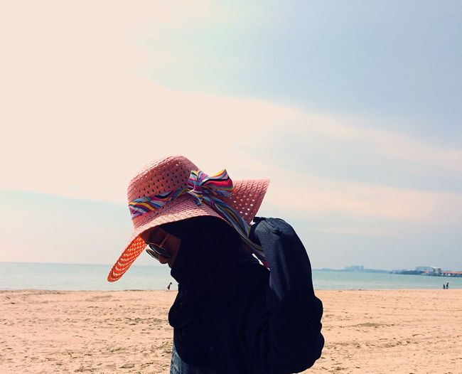 Teenage Girl Wearing Hat While Standing At Beach Against Sky