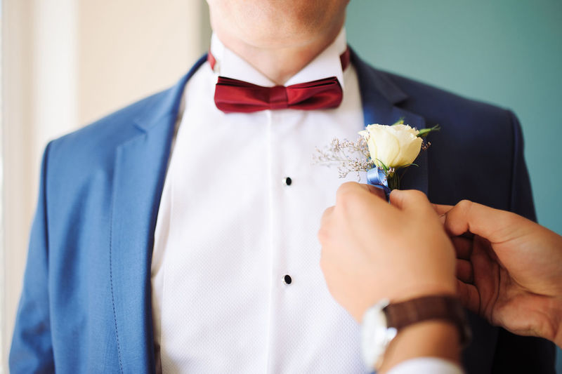 Midsection of man putting on a flower