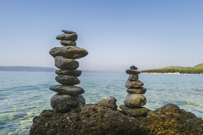 Rocks stacked on a sea shore Clear Water Beach Meditation Rock Formation Rock Stacking Balance Beauty In Nature Clear Sky Clear Sky Summer Day Close-up Day Nature No People Outdoors Rock - Object Scenics Sea Seascape Shoreline Sky Stack Sunny Summer Afternoon Tranquil Scene Tranquility Travel Destinations Water