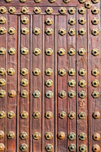 Full frame shot of metallic patterns on wooden door