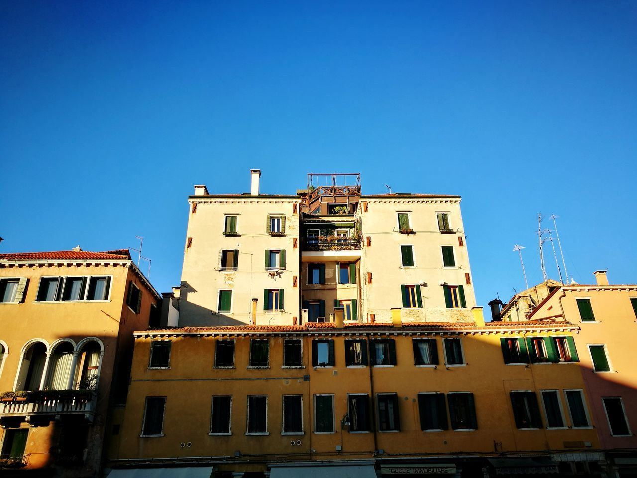 architecture, building exterior, built structure, window, clear sky, low angle view, residential building, blue, outdoors, day, balcony, no people, construction site, sky, city