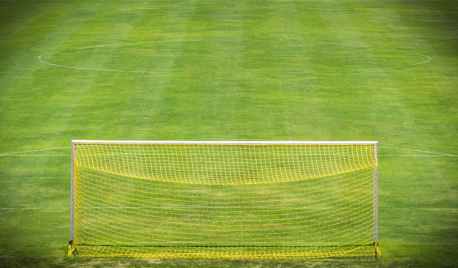 Goal net on green field Background Championship Field Football Game Gate Goal Goalkeeper Grass League Match Receation Shoot Soccer Soccer Field Sport Sports Stadium Stadium Team Tournament Win