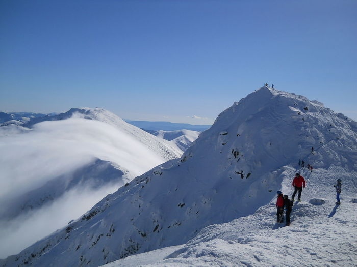 Tourists skiing on snow covered mountain against clear sky