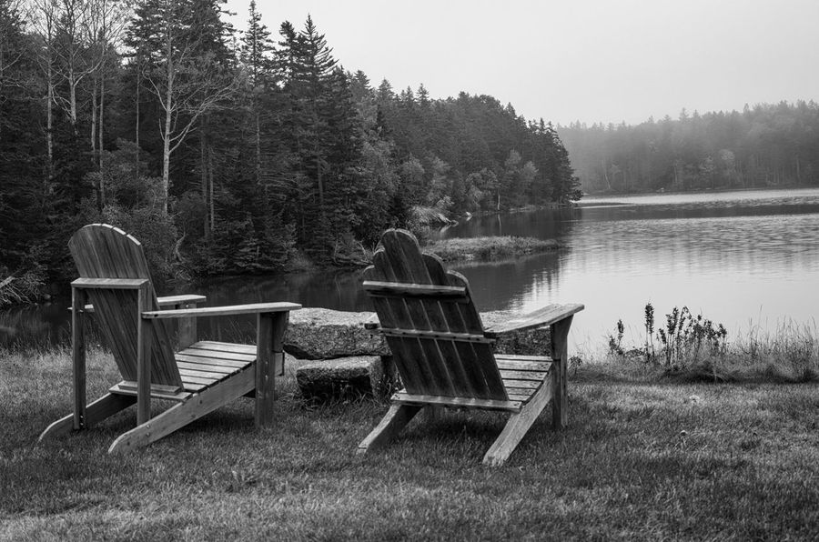 Black and white view over a pair of Adirondack chairs at a view of the water. Adirondack Chairs Black & White Beauty In Nature Blackandwhite Chair Day Grass Lake Monochrome Monochrome Photography Nature No People Outdoors Relaxation Scenics Tranquility Tree Water Water View