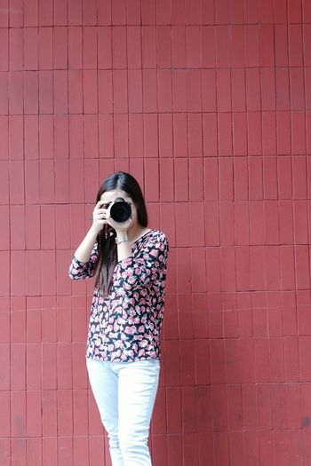 Young woman photographing against brick wall