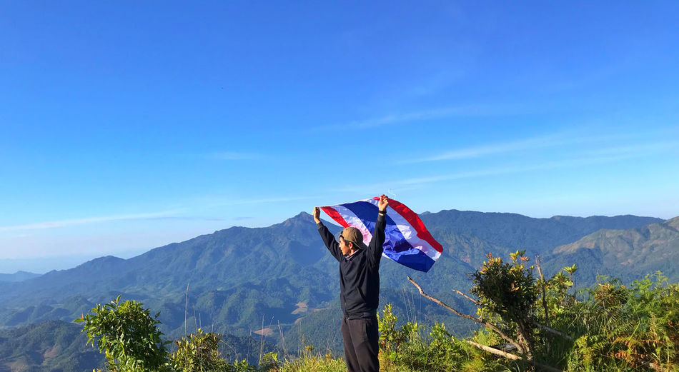 Man holding flag while standing by plants against mountains and blue sky