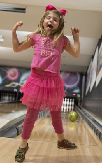 A six-year-old girl jumps for joy after bowling at Southern Illinois University at Carbondale at the Student Center. Arms Raised Bowl Bowling Cheerful Child Childhood Dancing Emotion Enjoyment Females Front View Full Length Girls Happiness Human Arm Indoors  Innocence Leisure Activity Lifestyles Mouth Open One Person Pink Color Real People Smiling Women