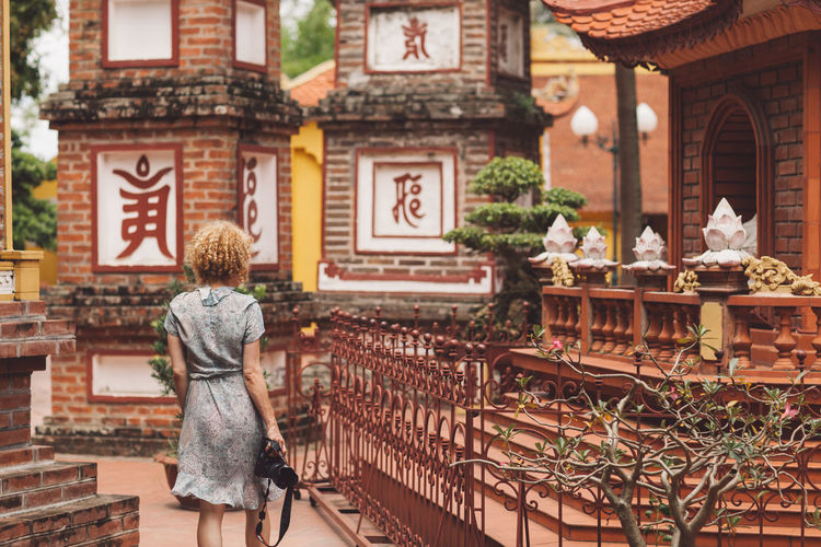 Rear view of woman walking at temple
