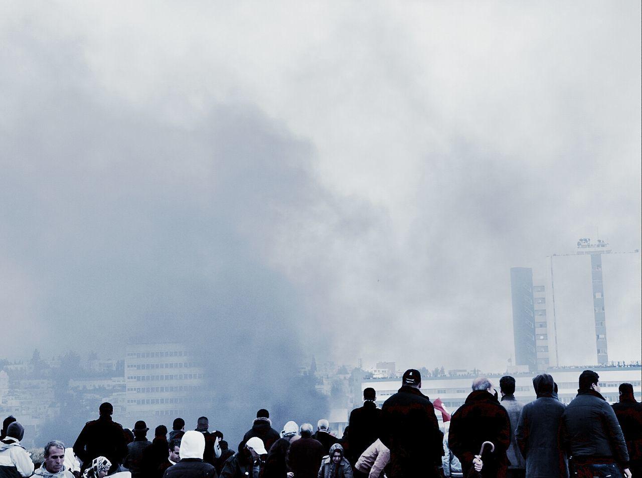 Rear view of people watching smoke