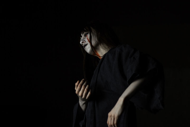 Young woman with halloween make-up against black background