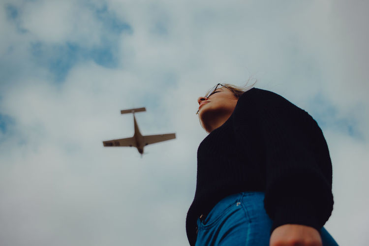 Low section of woman standing against airplane flying in sky