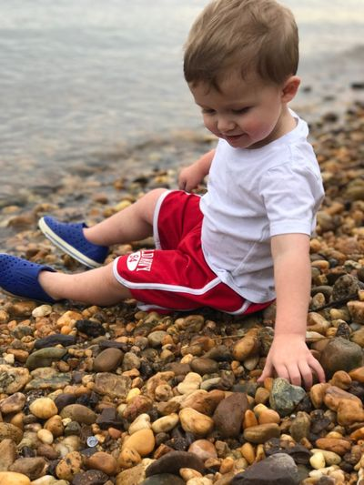 Dylan Matthew Beach North East Maryland Childhood Beach One Person Shore Pebble Real People Day Outdoors Full Length Boys Casual Clothing Sitting Sand Lifestyles Cute Sea Leisure Activity Sand Pail And Shovel Water Nature