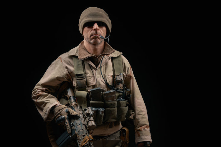special forces soldier of the united states poses with a rifle on a black background Soldier Warrior Adult Adults Only Armed Forces Army Assault Rifles Black Background Camouflage Clothing Gun Looking At Camera Men Military Military Uniform One Man Only One Person Only Men Outdoors People Portrait Special Forces Studio Shot War Weapon