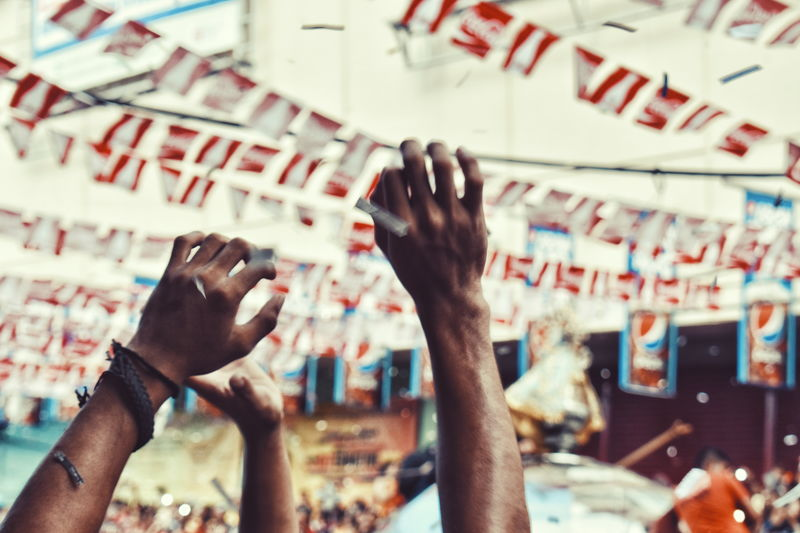 Cropped Image Of Men With Arms Raised Enjoying At Traditional Festival