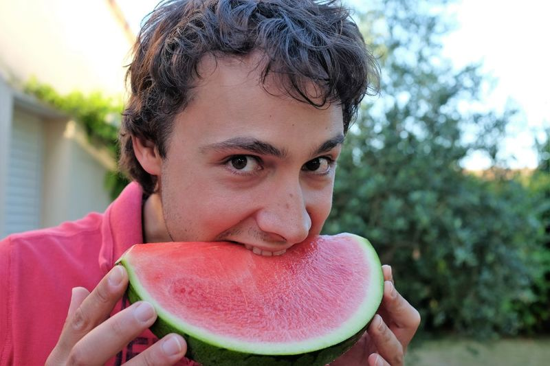 Close-Up Of Young Man Eating Watermelon