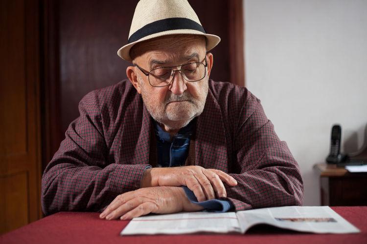 View Of Senior Man Reading At Table