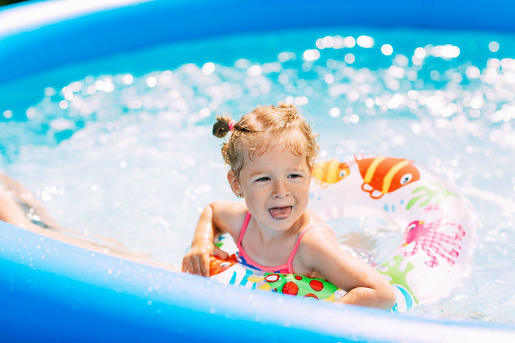 A laughing baby in a bright swimsuit learns to swim in the pool in the garden