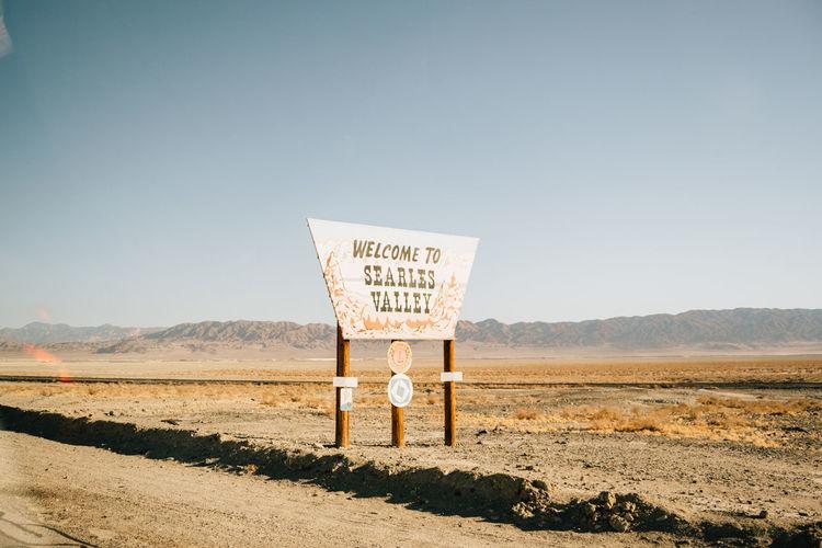 Information sign on landscape against clear sky