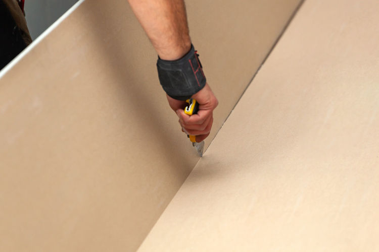 Cropped hand cutting plasterboard with work tool