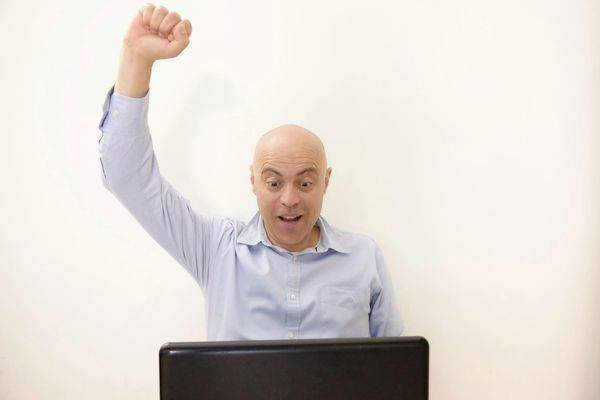 Man rejoices in front of the laptop Business Happy Adult Businessman Cheerful Communication Computer Concept Expression Exult Exultant Front View Happyness Human Arm Jubilant Laptop Men One Person Rejoicing Success Triumph