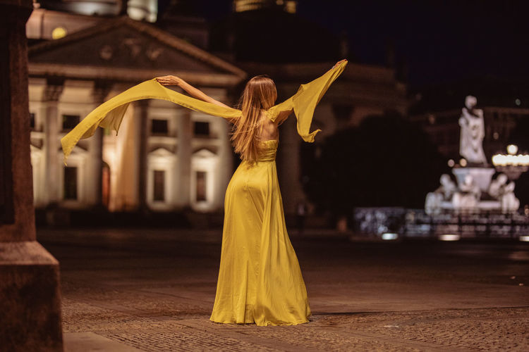 Rear View Of Female Model With Arms Outstretched Standing In City At Night
