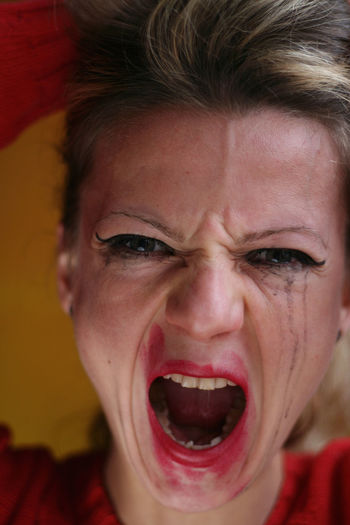 Close-up portrait of woman with smudged make-up screaming indoors