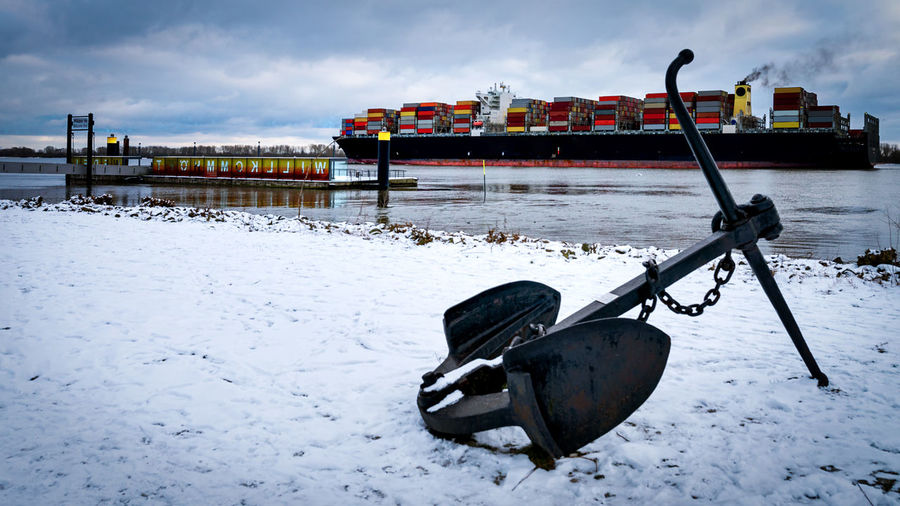 Boat moored on snow covered field against sky
