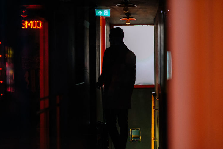 Rear view of silhouette man standing at entrance