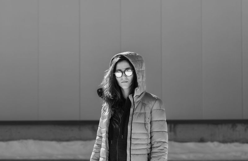 Portrait of woman wearing sunglasses and hooded jacket during winter