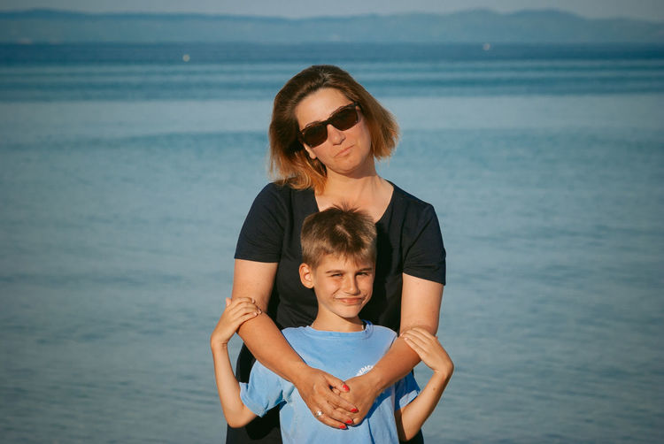 Portrait of woman with son standing at beach