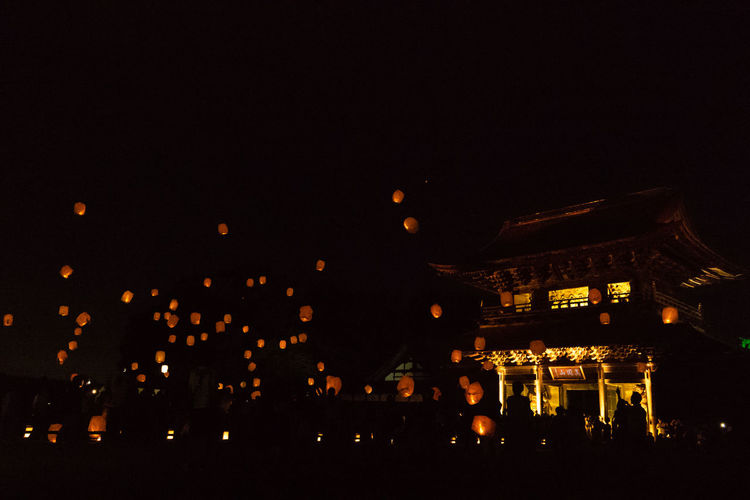 Illuminated paper lanterns flying against sky in city at night