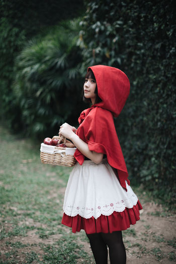 Full length of woman holding red basket while standing on field