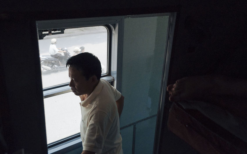 Man standing by train window against sky