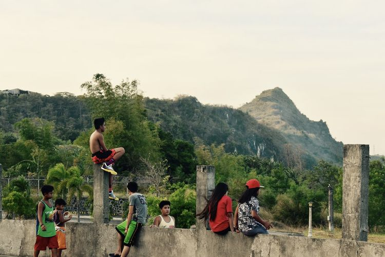 Children playing on mountain against sky