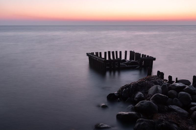 Broken dock Sunrise Dock Sea Water Horizon Horizon Over Water Sky Scenics - Nature Tranquil Scene Tranquility Sunset Beauty In Nature Nature Rock Beach Solid No People Rock - Object Idyllic Groyne