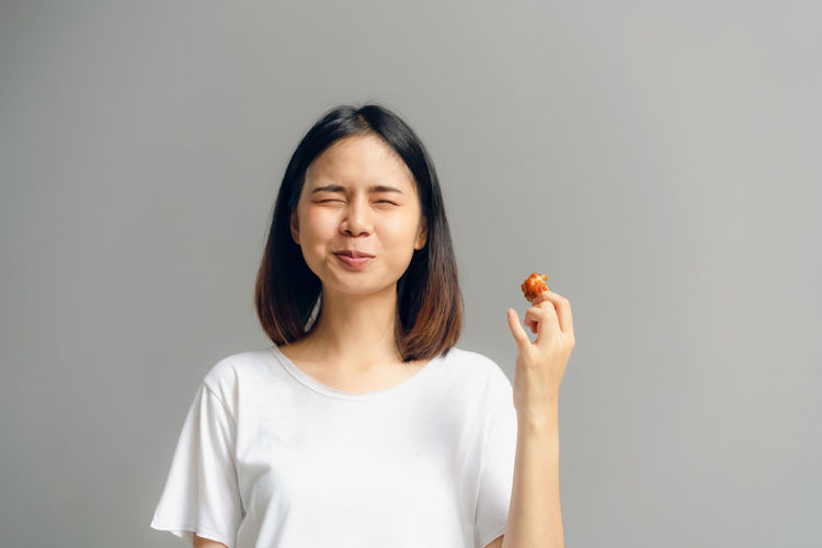 Young woman eating chicken while standing against gray background