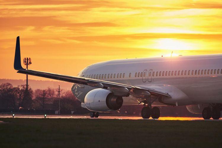 Airplane on airport runway against orange sky